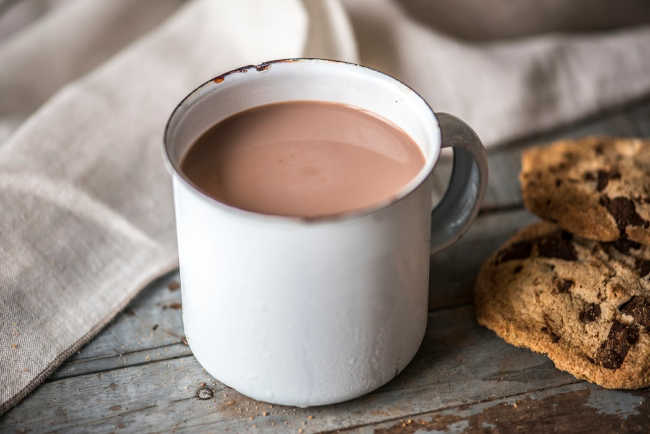 a white mug of hot chocolate next to some chocolate chip cookies