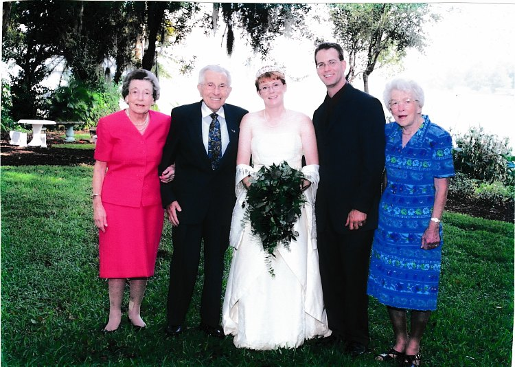 a bride and groom standing in a grass field with their grandparents