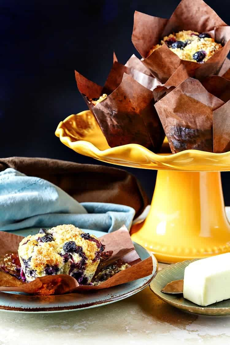 an orange cake stand piled with blueberry muffins in brown paper wrappers with one muffin on a plate