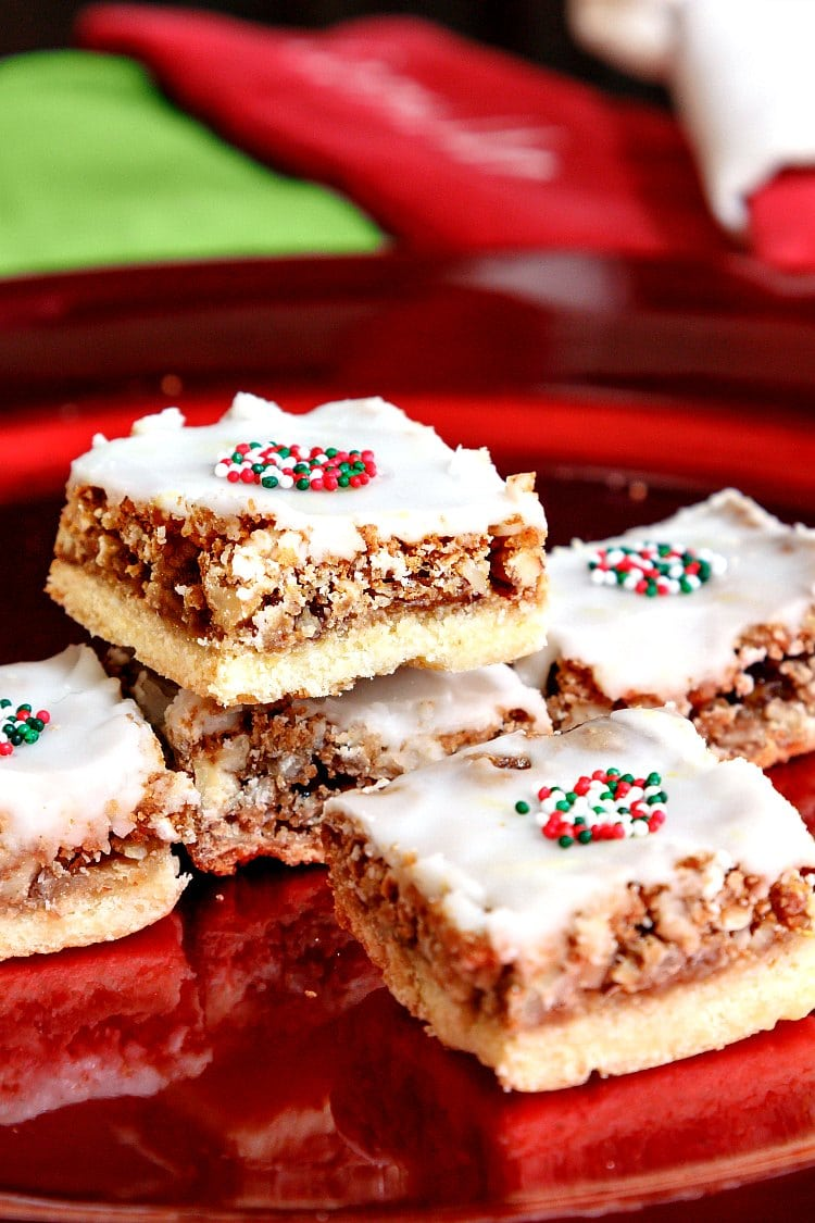 square angel slices bar cookies with white icing and some Christmas sprinkles on top stacked on a red plate