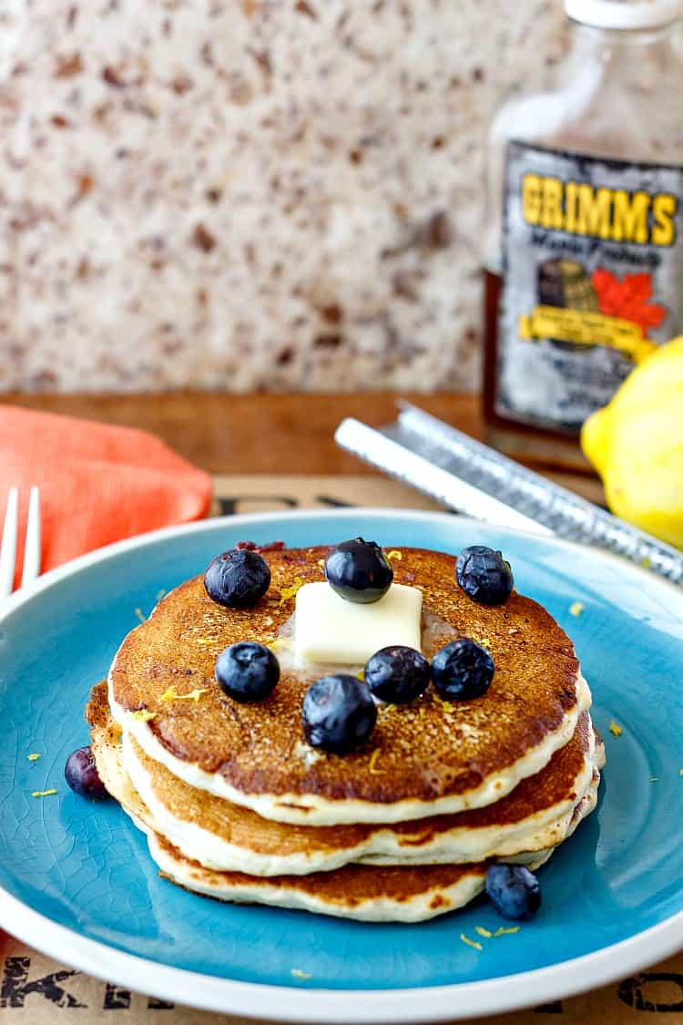 3/4 shot of stack of 3 pancakes for one on a blue plate with a pat of butter and fresh blueberries
