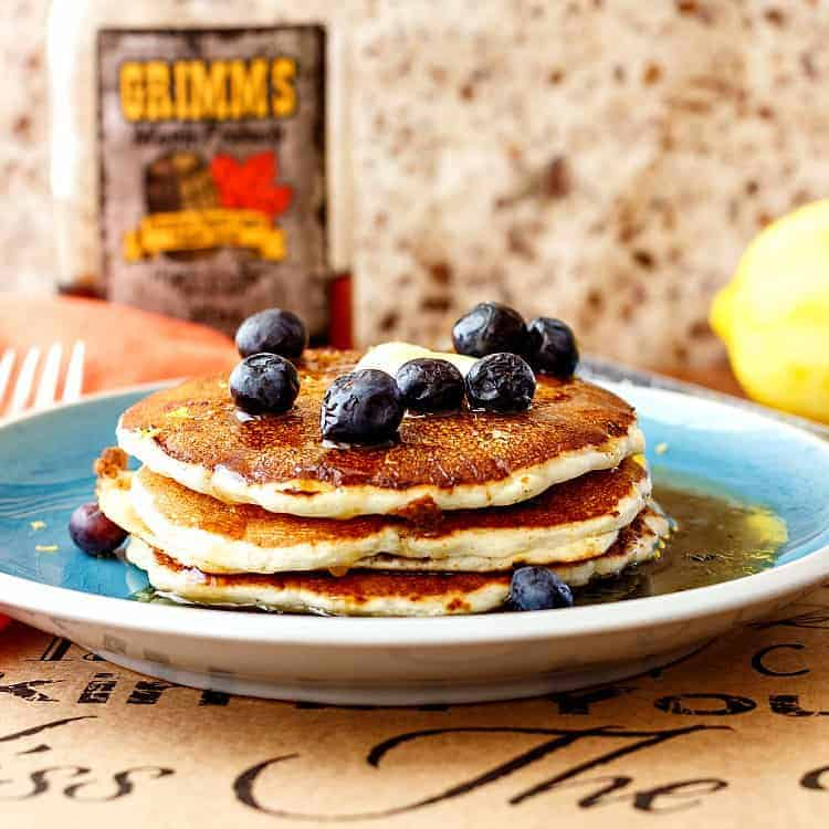 close shot of stack of three pancakes on a blue plate topped with a pat of butter and fresh blueberries
