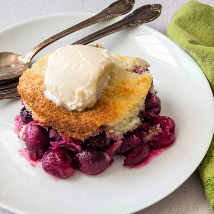 A serving of cobbler topped with vanilla yogurt with a spoon and a fork on the plate.