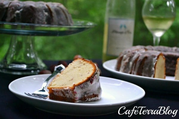 Grape Moscato Cake on a white plate with a cakestand and wine in the background