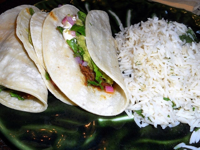 three beef cheek tacos on corn tortillas with cilantro rice on a green plate