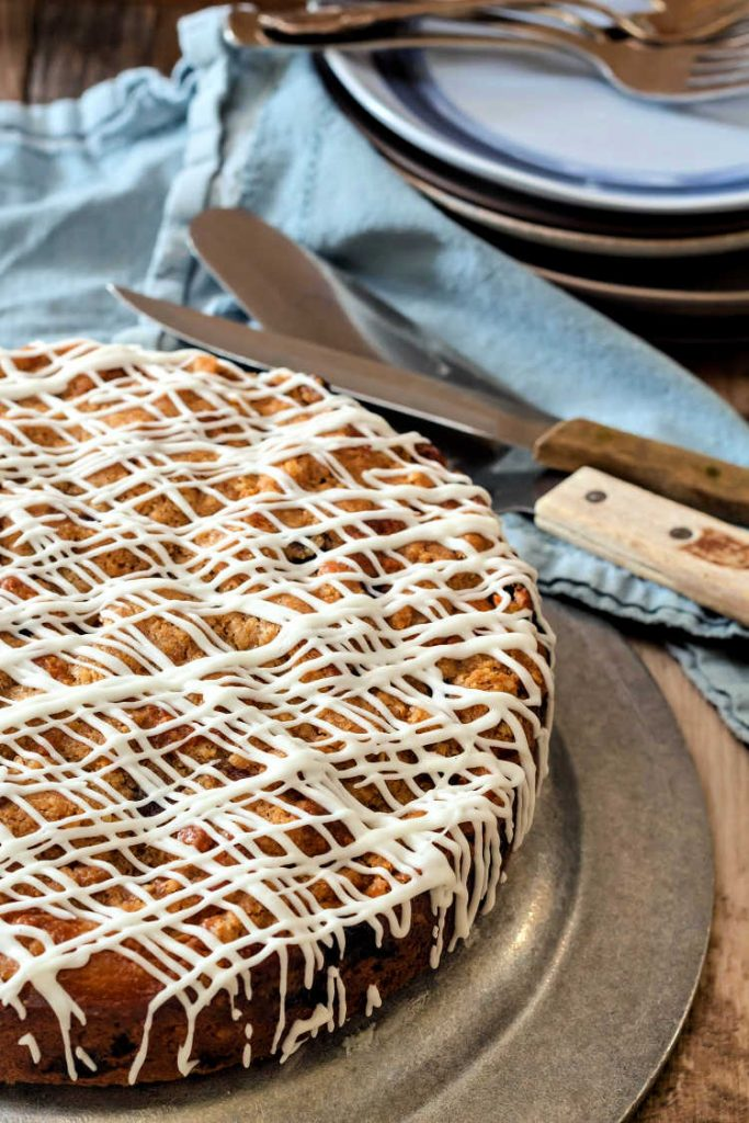 vertical image of browned butter blueberry buckle on a pewter tray with a blue napkin and a cake server