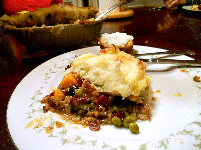 slice of thanksgiving turkey shepherd's pie with stuffing crust on a white plate along with a buttered corn muffin.