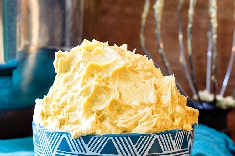 caramel buttercream frosting in a blue bowl with the mixer bowl and whisk in the background