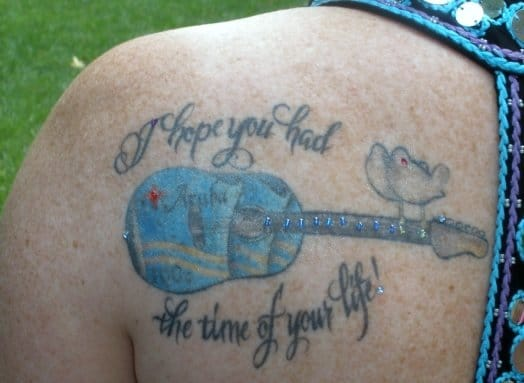 "Memorial Tattoo for Greg of a guitar and text reading ""I hope you had the time of your life."