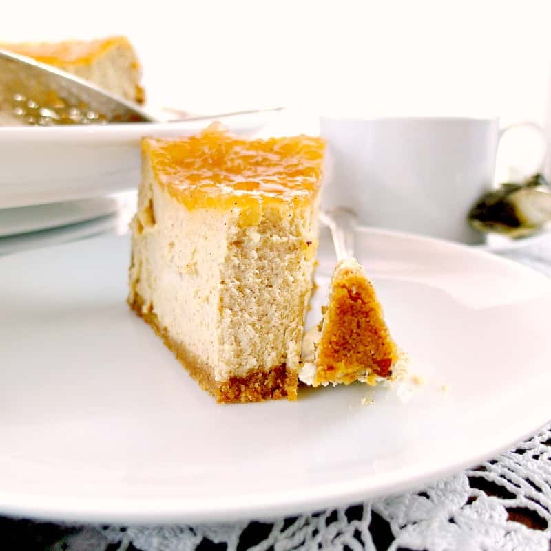 a slice of cinnamon buttermilk cheesecake with apple pie topping on it on a white plate