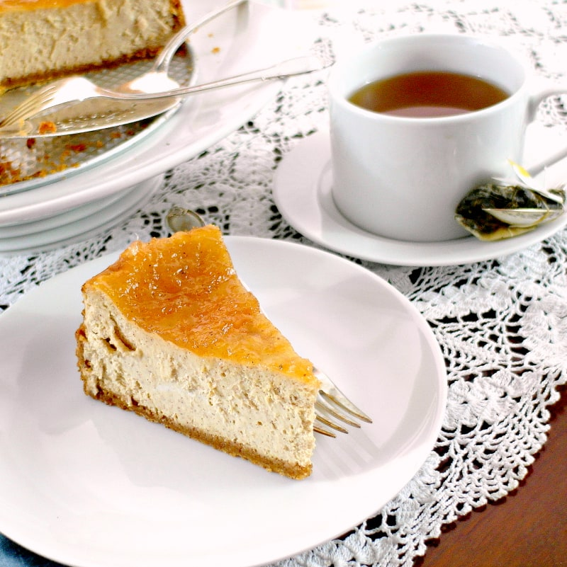 a slice of cinnamon buttermilk cheesecake on a white plate with a cup of tea