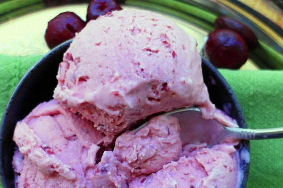 a scoop of sour cherry ice cream with cherries in the background