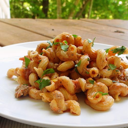 white plate with serving of creamy cavatappi pasta