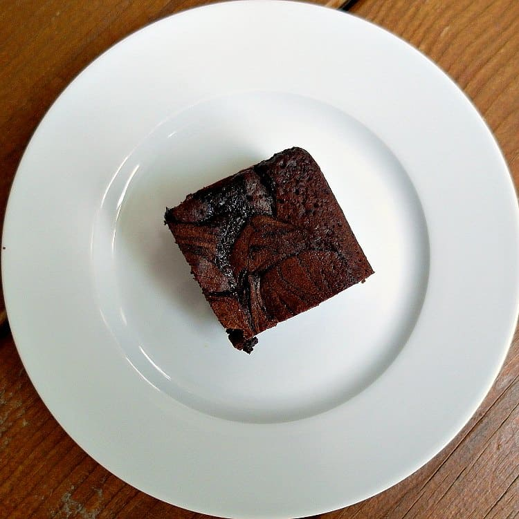 overhead shot of one square strawberry brownie on a white plate