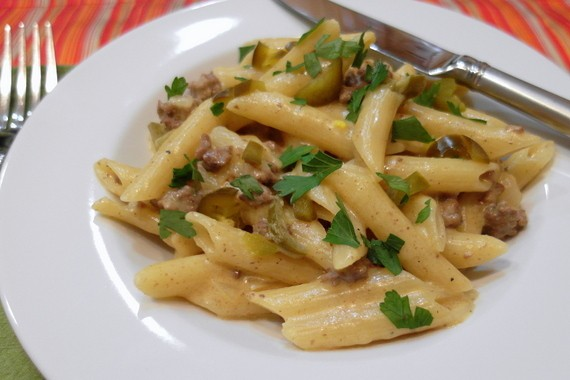 a white plate of pasta with ground beef