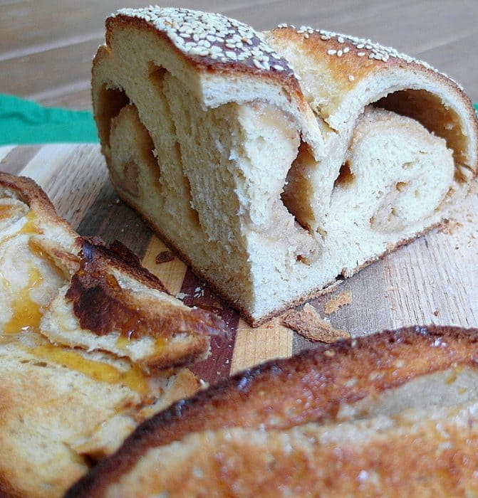 cut challah bread recipe with swirls of sweetened tahini inside and served with honey