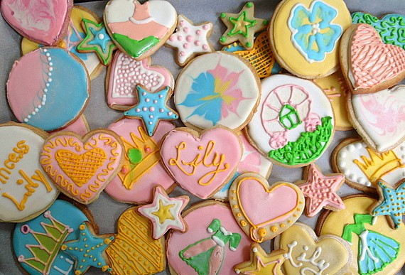 "an overhead shot of all colors of decorated cookies spread out on a baking sheet. Some say ""Lily"" or ""Princess Lily,"" others have hearts, crowns or princess dresses on them"