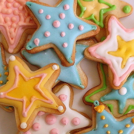 decorated shortbread cookies cut out in star shapes and decorated in different pastel colors
