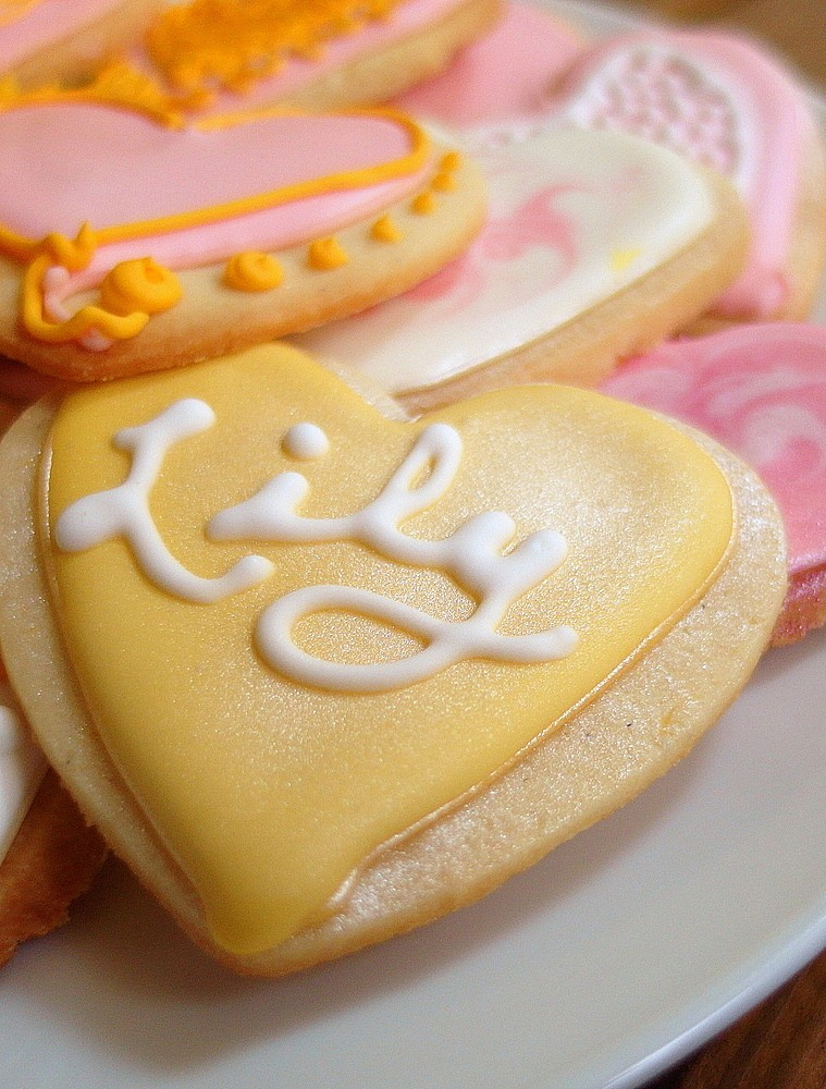 "closeup of a decorated heart-shaped cookie with pale yellow frosting and white cursive writing that spells ""Lily."""