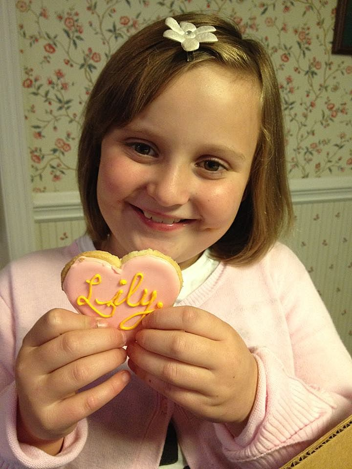 "a little girl with brown hair holding a heart shaped cookie decorated in pink frosting with ""Lily"" written in yellow."