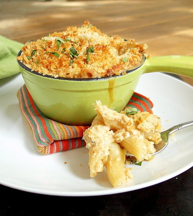 green ramekin of baked mac and cheese on a white plate