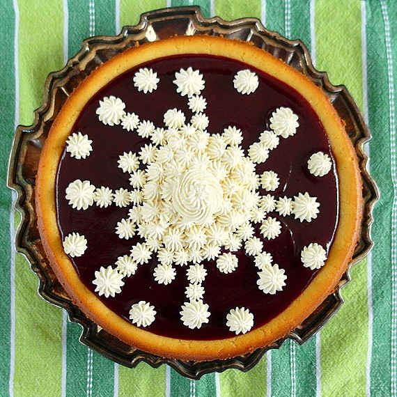 whole cheesecake spread with cranberry puree and decorated with mascarpone cream piped on to look like a big snowflake