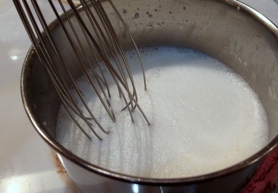 pan of milk with a whisk in it