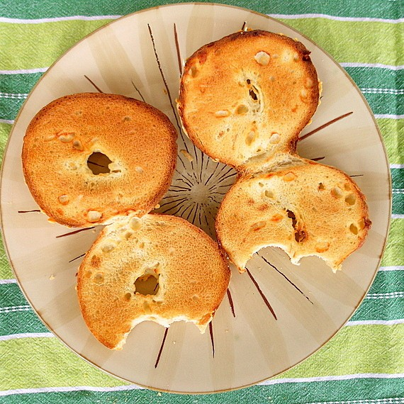 2 asiago cheese bagels, sliced and toasted on a plate