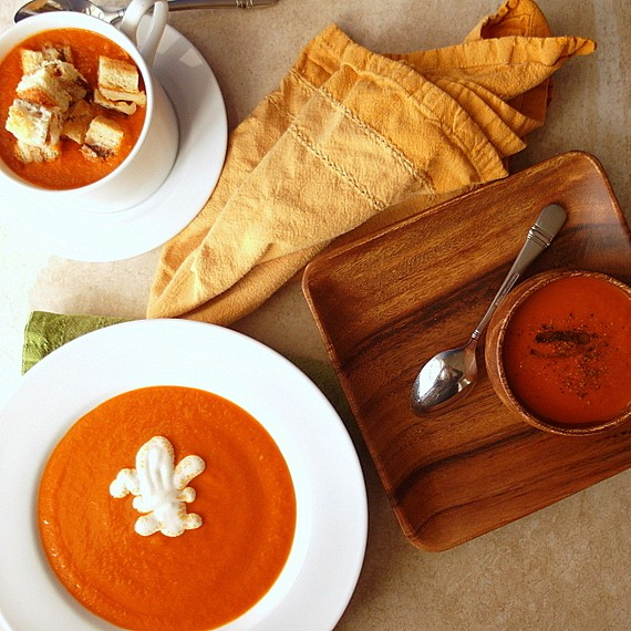 a mug of tomato soup with grilled cheese croutons, a small wooden bowl and a white rimmed bowl with tomato soup
