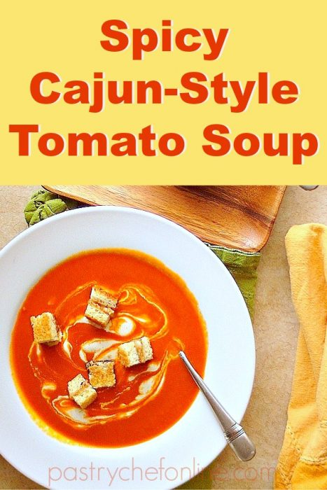 "pin image for cajun spicy tomato soup bowl of soup with croutons. text reachs ""spicy cajun-style tomato soup:"