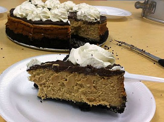 slice of cheesecake with ganache topping and whipped cream