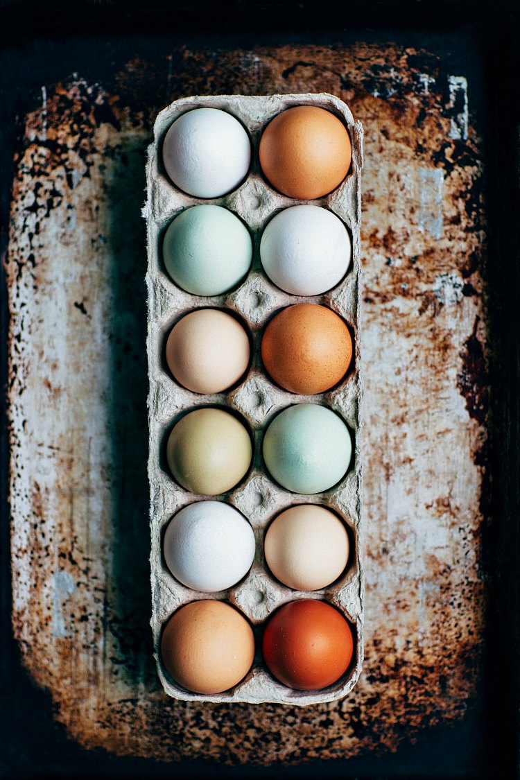 overhead shot of a dozen different colored eggs in a carton on a distressed background