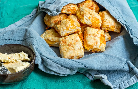 biscuits in a basket lined with a blue cloth napkin with butter