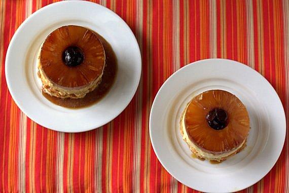 2 individual mini cheesecakes on white plates on an orange striped background