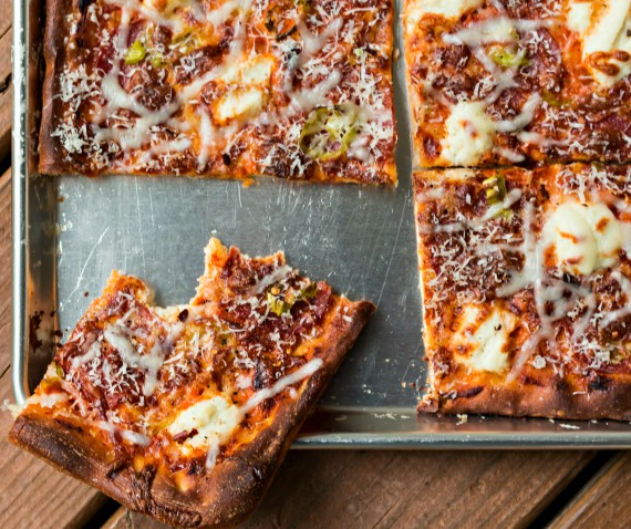 baked grandma pizza recipe made with vodka sauce and topped with cheese and pepperoncini on a baking sheet