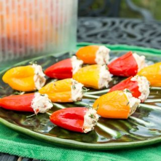A green plate of cheese stuffed pickled peppers.