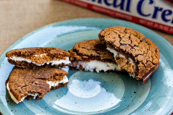 Two oatmeal creme pie cookies torn in half on a blue plate with a box of Little Debbies in the background