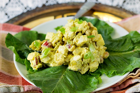 close up of chicken salad in curried dressing with nuts and fruit on lettuce leaves