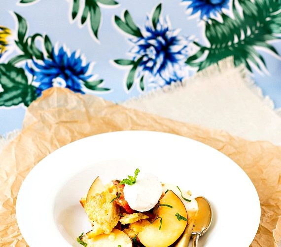 Bowl of peach panzanella with cornmeal biscuits.
