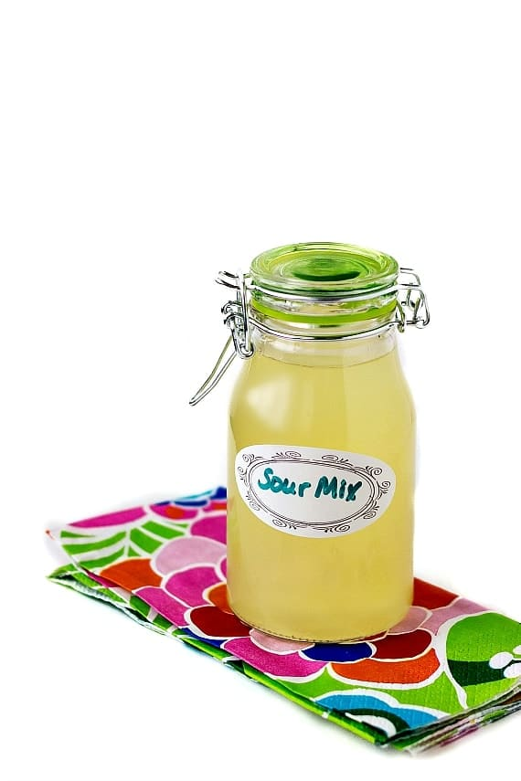 """a bottle of homemade sour mix on a floral napkin. Label on the bottle reads """"Sour Mix"""""""
