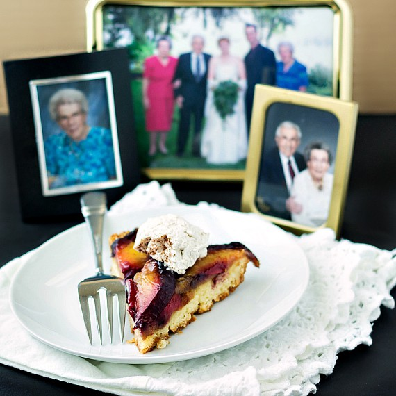 slice of German plum cake on a white plate with family photos in the background.