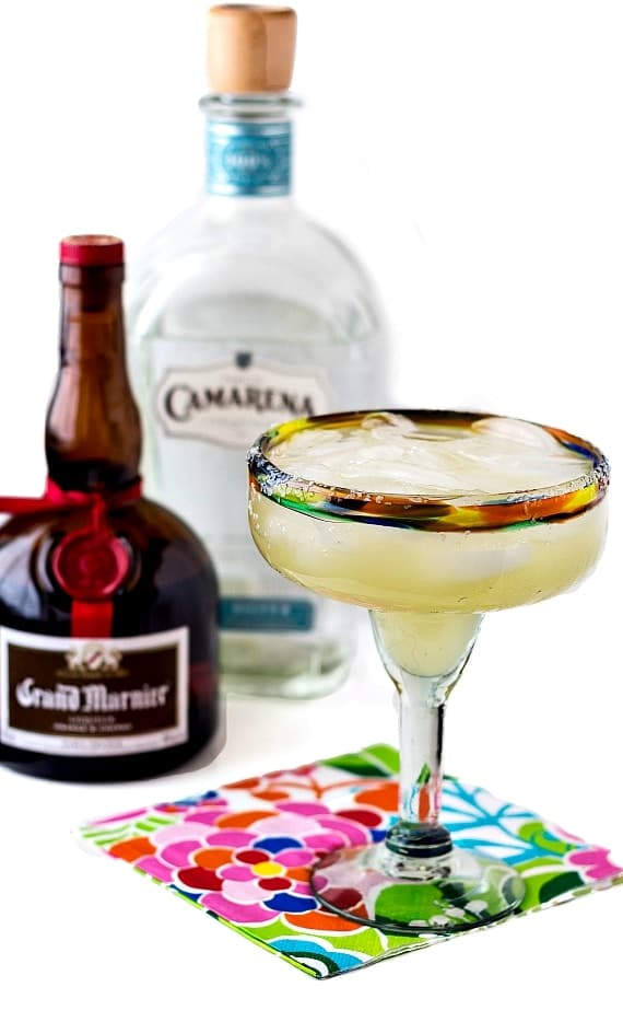a full margarita glass on a floral napkin with a bottle of Grand Marnier and one of Camarena tequila in the background