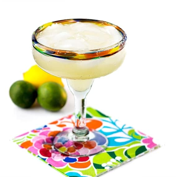 a top shelf margarita on a floral napkin with 2 limes and 1 lemon in the background
