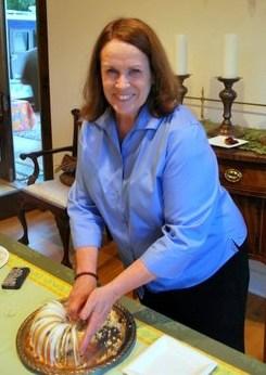 a photo of Nandcie McDermott slicing the blueberry lemongrass pound cake