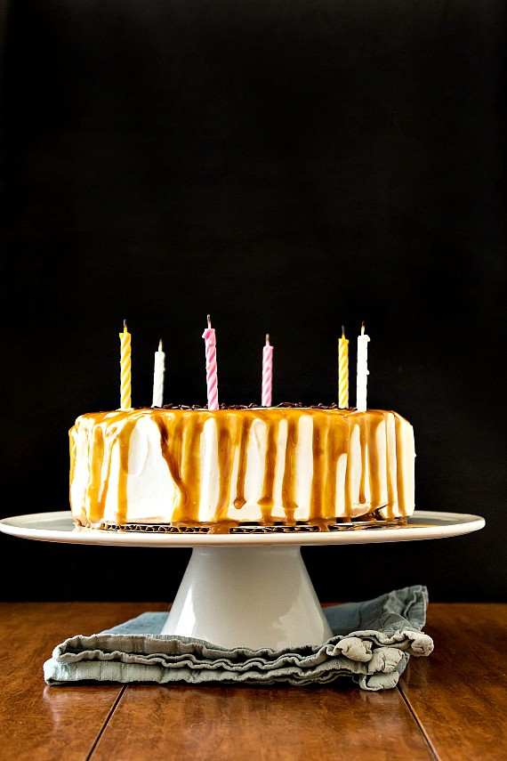 ice cream cake with candles on a white cake stand