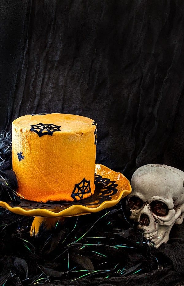 """an orange frosted chocolate Halloween cake decorated with edible """"paper"""" spiders and spider webs"""