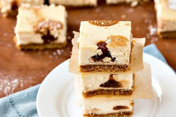 stack of three cheesecake bars on a white plate with polka dots of apple butter