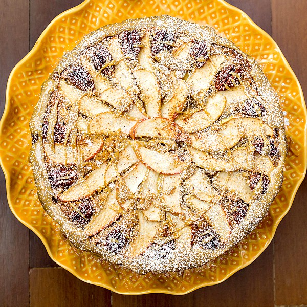 overhead shot of the top of spiced apple cake showing a decorative arrangement of apple slices and pecans on top