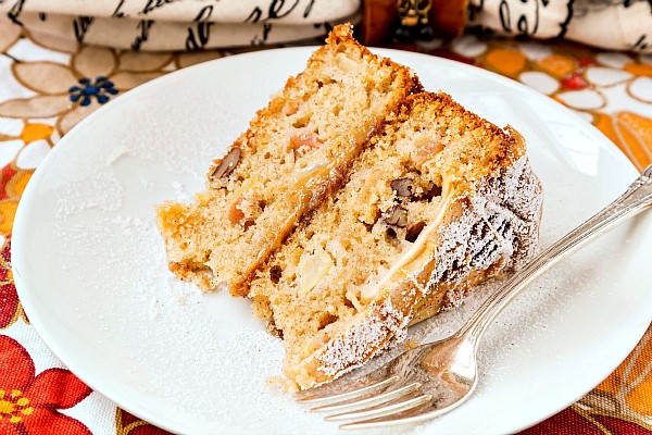 a slice of spiced apple cake on a white plate