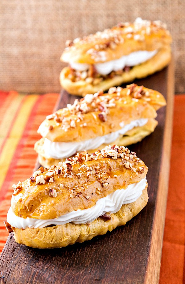 3 pecan pie eclairs on a wooden board